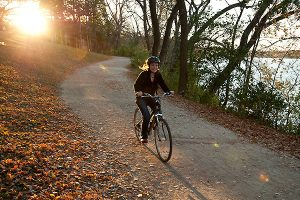 Late afternoon sunlight backlights a person biking along the Howard Temin Lakeshore Path at the University of Wisconsin-Madison during autumn on Oct. 13, 2010. (Photo by Jeff Miller/UW-Madison)
