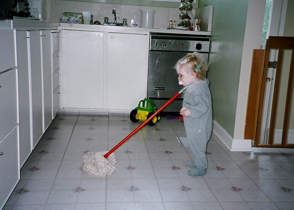 Child holding mop in kitchen