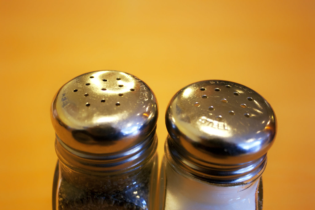 Salt and pepper shakers in front of a yellow background