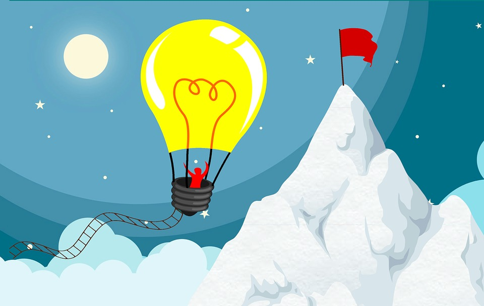 Person in a lightbulb-shaped hot air balloon drifting towards their goal, marked by a red flag.